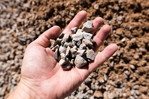 person holding crushed stone