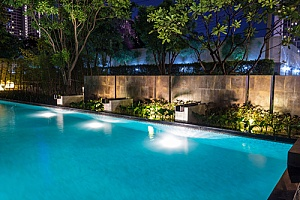 a fancy backyard pool lit up at night