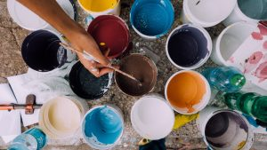 buckets of paint being used to paint a home