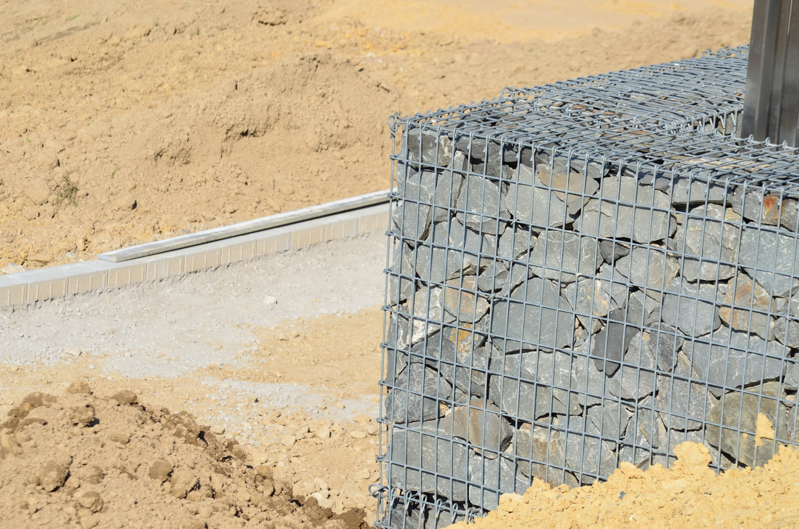 Wire wrapped stone retaining wall.