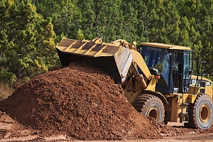 a bulldozer moving dirt to fill a hole in a yard