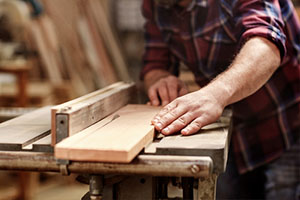hands of a craftsman cutting a wooden plank