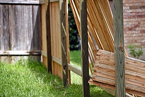 Lumber leaning up against fence posts