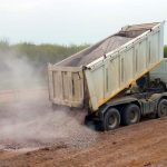 construction materials being transported through dump truck hauling services