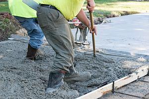 Men paving concrete driveway