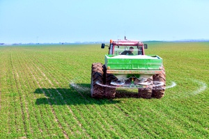 a tractor on a large field that contains acidic soil levels