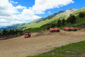 Orange Dump trucks leveling the slope by filling dirt