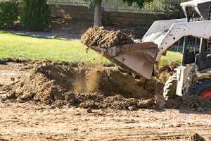 a Bulldozer filling dirt after pool removal
