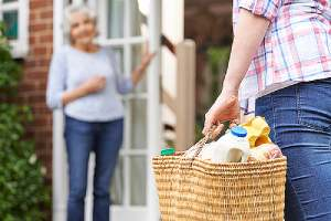 A Person helping his elderly neighbor. Communicating early and often with your neighbors about your home addition plan