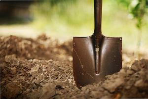 A shovel and soil. Soil acidity refers to how acidic or alkaline the soil is in your lawn and garden