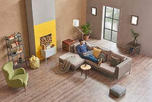 Man is in his spacious living room. A home addition adds more space to your home