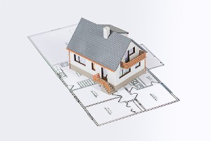 Model house of a custom home addition project on a blueprint