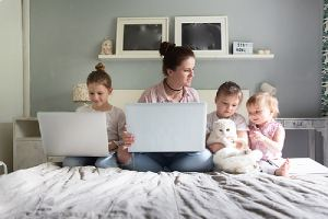Mom and her three children are sitting on bed with laptops in their newly added home addition