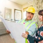 A bathroom remodeling contractor talking with female client over blueprint plans