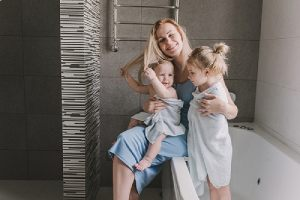 A happy mother with two of her little daughters in the bathroom. Remodeling cost of bathroom can be expensive
