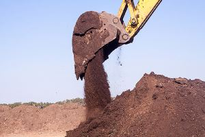 A large iron excavator pours dirt. Fill dirt is different than your everyday dirt on the ground