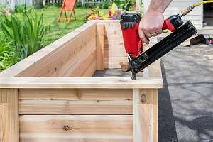 Closeup of a man using a pneumatic nail gun. A DIY Outdoor Projects concept