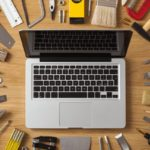 Construction tools all around a laptop. DIY outdoor projects concept