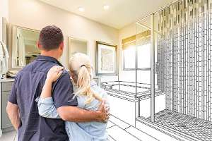 Couple and a bathroom remodel blueprint on the background