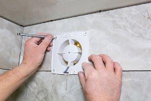 Worker installing half bathroom wall ventilation