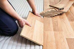 Worker installing laminated wood floor. Laminate flooring is one of the best flooring option for bathroom remodel