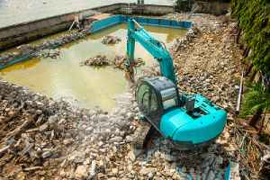 Swimming pool being demolished by Backhoe. A full pool removal is a more expensive method
