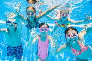 little kids swimming in pool underwater