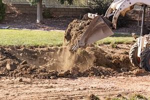 small bulldozer digging in yard for pool installation