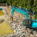 swimming pool being demolished by backhoe for rebuilding