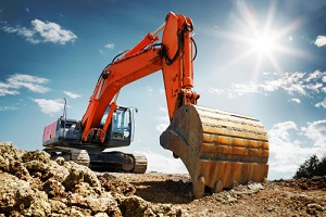 crawler excavator front view digging on demolition site in backlight