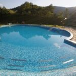 swimming pool in backyard with hot tub