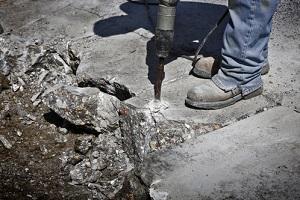 man drilling cement concrete road