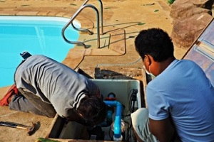 technicians removing the pool pump
